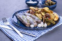 在板材的鲱鱼内圆角,烘烤在烤箱土豆和腌汁 荷兰的可口传统食物 在a的荷兰纤巧 库存图片