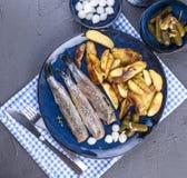 在板材的鲱鱼内圆角,烘烤在烤箱土豆和酱瓜和葱 荷兰的可口传统食物 免版税图库摄影