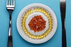 在板材的黄色和红色药片 免版税库存照片