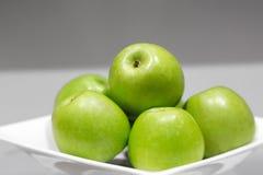在板材的绿色苹果 库存图片