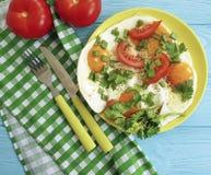 在板材葱,面包开胃菜蕃茄,刀子叉子,蓝色木背景,毛巾,荷兰芹的煎蛋 库存图片