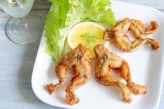 在板材食物概念的油煎的青蛙腿 免版税图库摄影