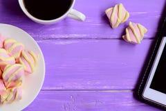 在板材,一杯咖啡的一点蛋白软糖,在木背景的片剂与文本的拷贝空间 女性工作场所 免版税图库摄影