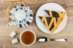 在板材,茶壶,茶的越桔饼,多块的糖 免版税库存照片