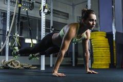 在板条的有吸引力的肌肉妇女CrossFit教练员立场在锻炼期间 库存照片