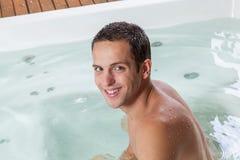 在极可意浴缸里面的愉快的人 免版税库存照片