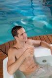在极可意浴缸饮用的汁液里面的人 免版税库存照片