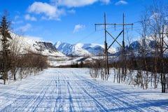 在极性山和老电柱子的冬天路 免版税库存照片
