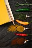 在构成笔记本食谱的和东方香料的顶视图在匙子和胡椒在黑金属盘子在亚洲样式 免版税库存照片