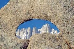 在构筑惠特尼峰和多雪的山脉山的岩石的阿拉巴马小山孔在日出在孤立杉木,加州附近 免版税库存照片