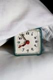 在枕头之下的闹钟在河床上 免版税库存图片