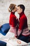 在枕头围拢的红色圣诞节套头衫亲吻的夫妇 免版税库存照片