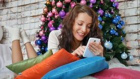 在枕头在圣诞树附近装饰用桃红色紫色球和浏览有她的卷曲浅黑肤色的男人互联网 影视素材