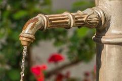 在林道浇灌流动从在街道上的管子 免版税库存图片