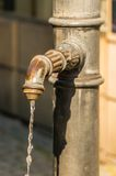 在林道浇灌流动从在街道上的管子 免版税库存照片
