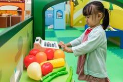 在果子商店的亚洲中国小女孩角色扮演 免版税库存照片
