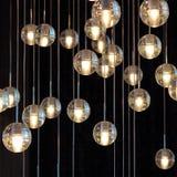 在枝形吊灯的照明设备球在灯光,电灯泡垂悬从天花板的,在黑暗的背景的灯,有选择性 免版税图库摄影