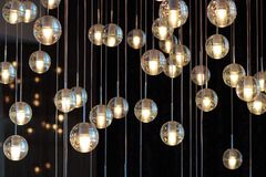 在枝形吊灯的照明设备球在灯光,电灯泡垂悬从天花板的,在黑暗的背景的灯,有选择性 库存图片