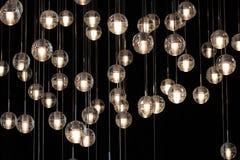在枝形吊灯的照明设备球在灯光,电灯泡垂悬从天花板的,在黑暗的背景的灯,有选择性 库存照片