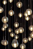 在枝形吊灯的照明设备球在灯光,电灯泡垂悬从天花板的,在黑暗的背景的灯,有选择性 图库摄影