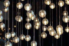 在枝形吊灯的照明设备球在灯光,电灯泡垂悬从天花板的,在黑暗的背景的灯,有选择性 免版税库存照片
