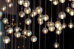 在枝形吊灯的照明设备球在灯光,电灯泡垂悬从天花板的,在黑暗的背景的灯 图库摄影