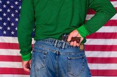 在枪的手有旗子的 免版税库存图片