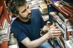 在架子之间的好奇人阅读书在图书馆里 免版税库存图片