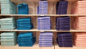 在架子在桃红色,蓝色和紫色颜色的蓬松沐浴的毛巾堆积的待售在商店 库存照片