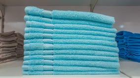 在架子在蓝色和深蓝颜色的蓬松沐浴的毛巾堆积的待售在商店 免版税库存图片