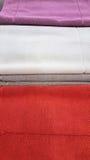 在架子在紫色,白色,灰色和红颜色的蓬松沐浴的毛巾堆积的待售在商店 库存图片