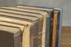 在架子堆积的旧书正面图  没有标题和作者的书 站立在架子的旧书看法  免版税图库摄影