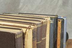 在架子堆积的旧书正面图  没有标题和作者的书 站立在架子的旧书看法  免版税库存照片