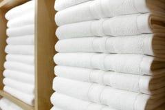 在架子折叠和堆积的新鲜的白色旅馆毛巾 免版税库存图片