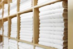 在架子折叠和堆积的新鲜的白色旅馆毛巾 库存图片
