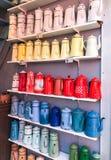 在架子排队的多彩多姿的水壶收藏 免版税库存照片