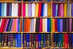 在架子显示的五颜六色的织品在商店 免版税库存图片