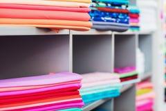 在架子的五颜六色的衣裳在商店 免版税图库摄影