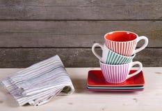 在架子的五颜六色的镶边咖啡杯 库存图片