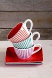 在架子的五颜六色的镶边咖啡杯 库存照片