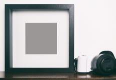 在架子的厚实的空白的黑照片框架与照相机 免版税库存照片