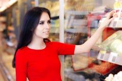 在架子的妇女购物在超级市场商店 免版税库存图片