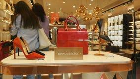 在架子的特写镜头古典妇女鞋子袋子在现代商店 股票录像