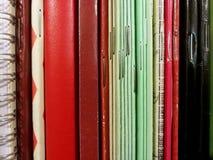 在架子的红色,绿色和黑暗的减速火箭的笔记本 免版税库存图片