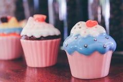 在架子的装饰陶瓷杯形蛋糕在咖啡馆 免版税图库摄影
