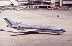 在柏油碎石地面的减速火箭的东航波音727 免版税库存照片