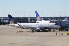 在柏油碎石地面的团结的明确巴西航空工业公司飞机在芝加哥奥黑尔国际机场在芝加哥 库存照片