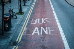 在柏油碎石地面的老公车专道标号在伦敦 免版税库存图片