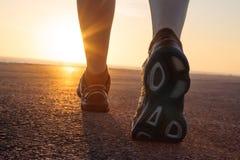 在柏油碎石地面的跑鞋与日落 库存照片