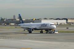 在柏油碎石地面的JetBlue飞机在约翰・肯尼迪国际机场在纽约 免版税库存照片